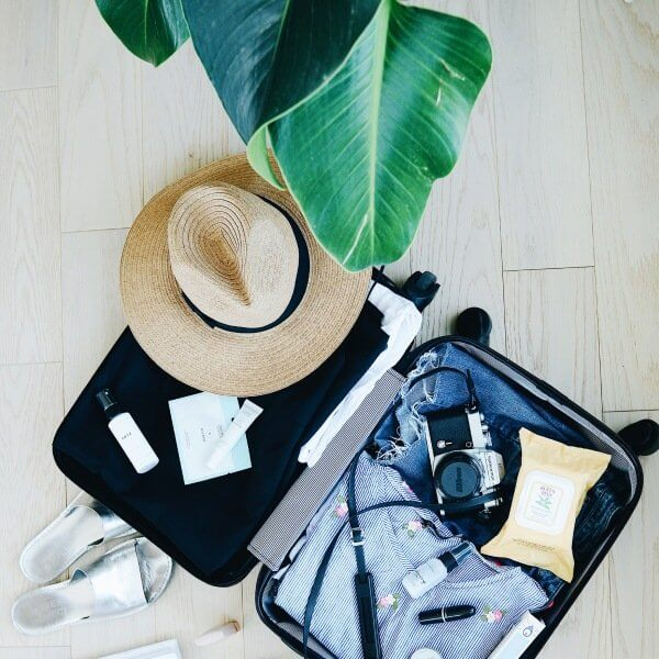 Travel Great- hat and an open suitcase for Sharing the Wander