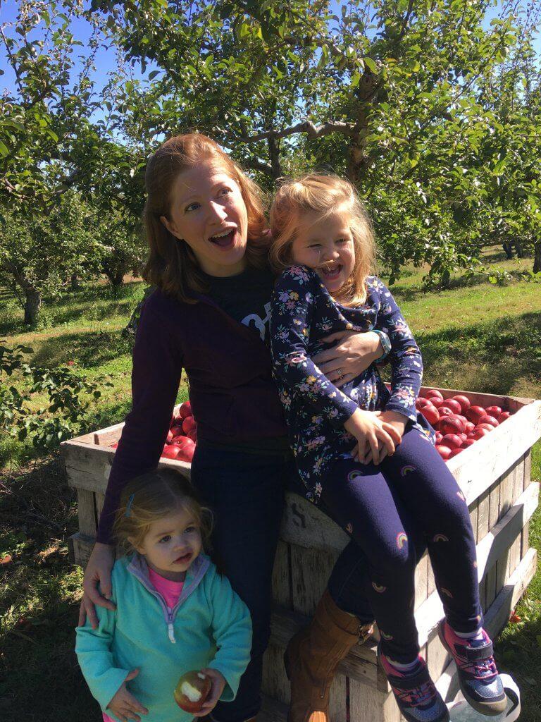 Cynthia, S, E having fun in an apple orchard