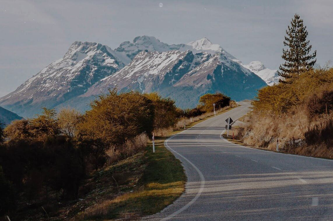 road between trees near snow capped mountains